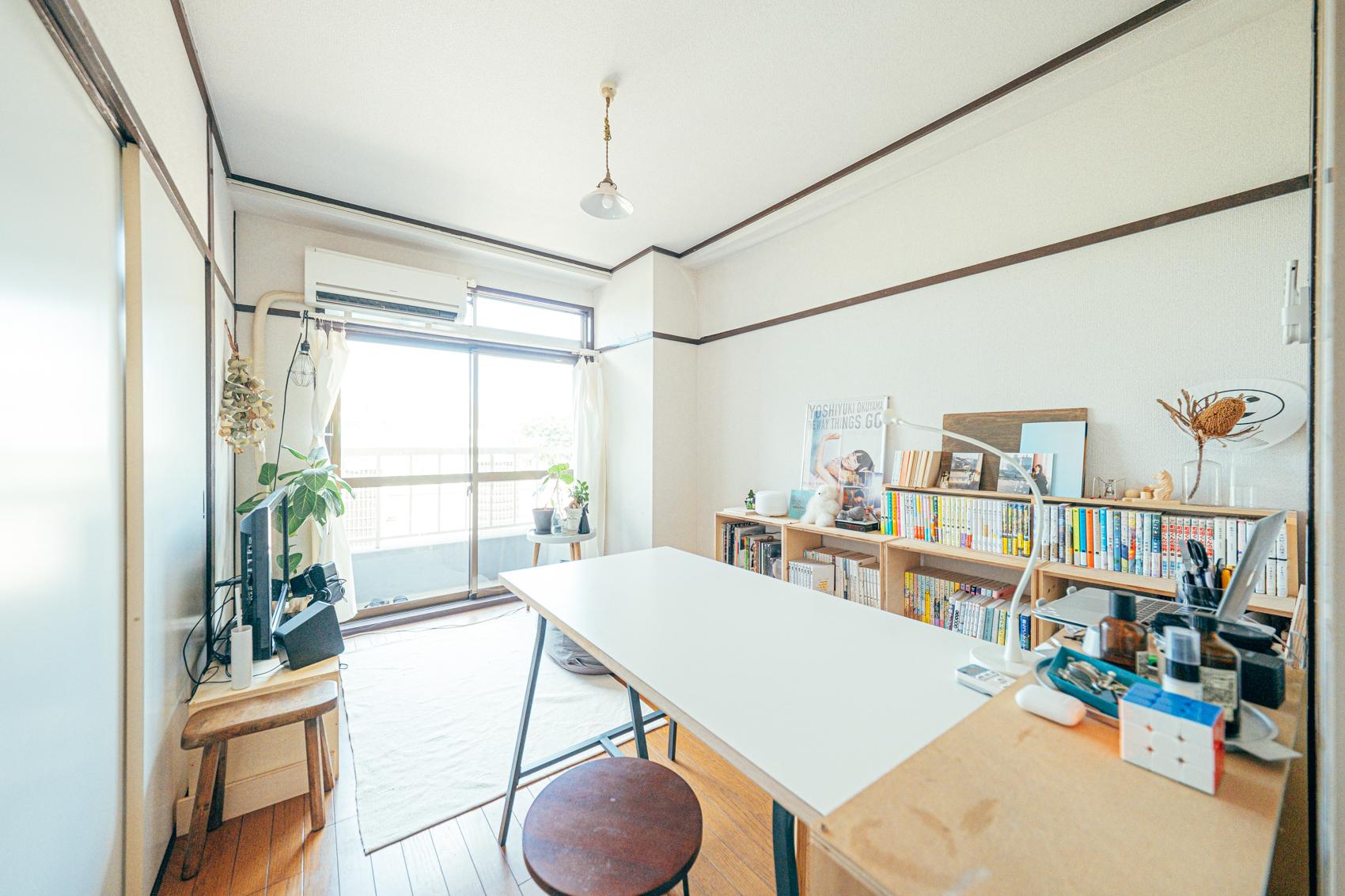 リビングは壁一面の本棚が広がる、リラックススペース兼ダイニングスペース。パソコン作業などはこのダイニングテーブルで行っています。以前住んでいたところよりもぐんと広くなった分、大好きなインテリアを楽しめるようになったのだそう。