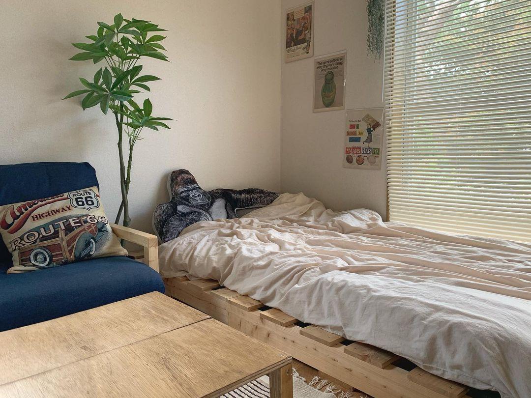部屋が広く見えるように、家具の高さはなるべく低く。ベッドは木製パレットを並べ、ソファも脚をカットしてロースタイルにしています。ローテーブルは端材を組み合わせて作ったもので、サイズ感もよく愛着があるそう。