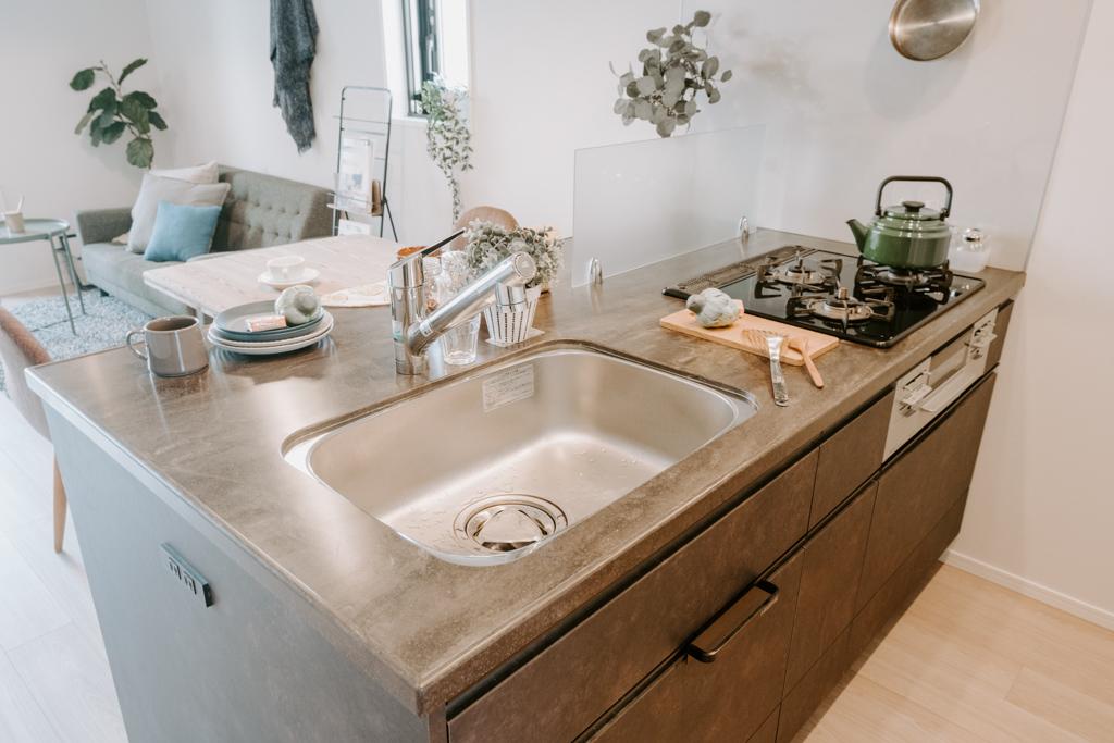 キッチンはシンクが大きく、3口コンロでグリル付き。奥行きがたっぷりとあるので、コーヒーメーカーなどのちょっとした器具も置けるゆったり感がいいですね。汚れも目立たない、人造大理石を使用した天板です。