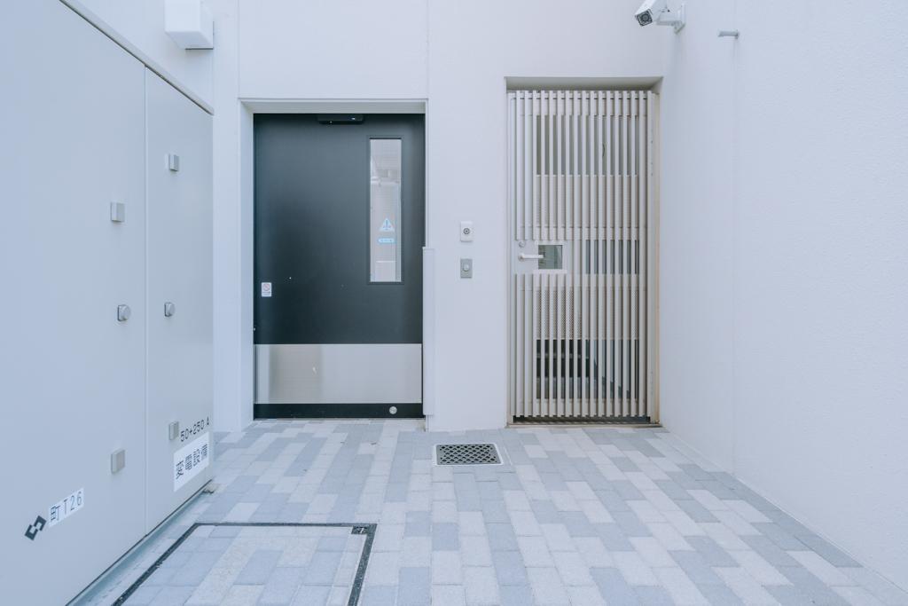 駐輪場や足洗い場へ入るための裏口のゲート。監視カメラがあったり、鍵がないと中に入れなかったりと、セキュリティを第一に考えられたつくりになっています。