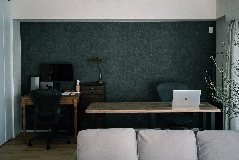剥がせる壁紙を貼られたグレーの壁の前に、アンティークのデスクと、DIYの大きなテーブルを配置。壁にぴったりと収めることもできるサイズに計算されています。広々としたワークトップは撮影に使われたり、二人それぞれが好きな場所で作業したりとフレキシブルに使える空間に。(このお部屋はこちら)