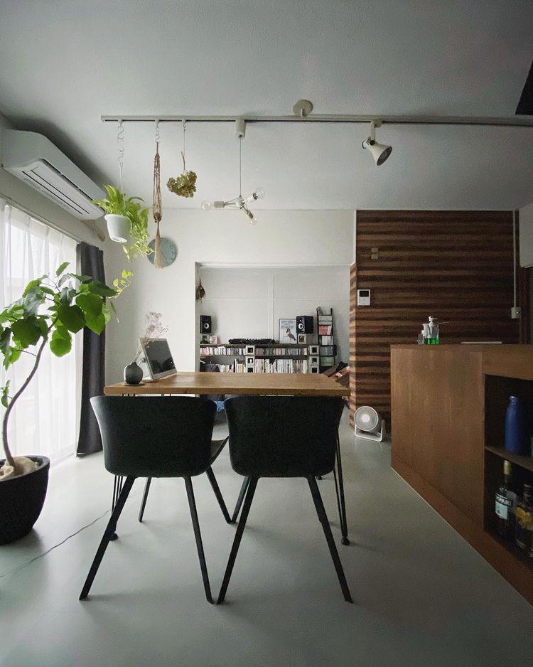 2LDKのリノベーションされたお部屋で二人暮らしをする方の事例。窓に対して左半分がダイニング、右半分が趣味を楽しむスペースという配置。通常サイズのテレビは置かず、ポータブルサイズのものをダイニングテーブルに乗せて使用しています。