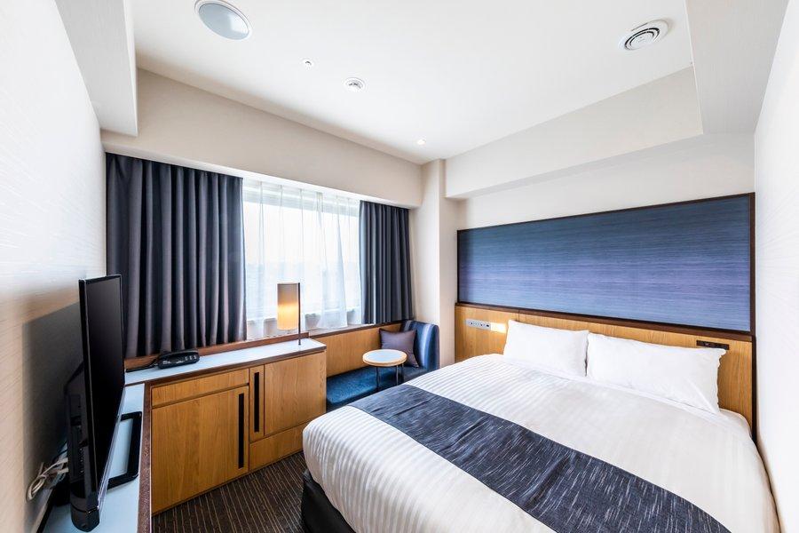 ダブルベッドが置かれた室内はデザイン性が高く洗練された印象。ベッドだけでなく、窓際にソファスペースもあるので、コーヒーを一杯、ゆっくり飲んだりもできそうです。