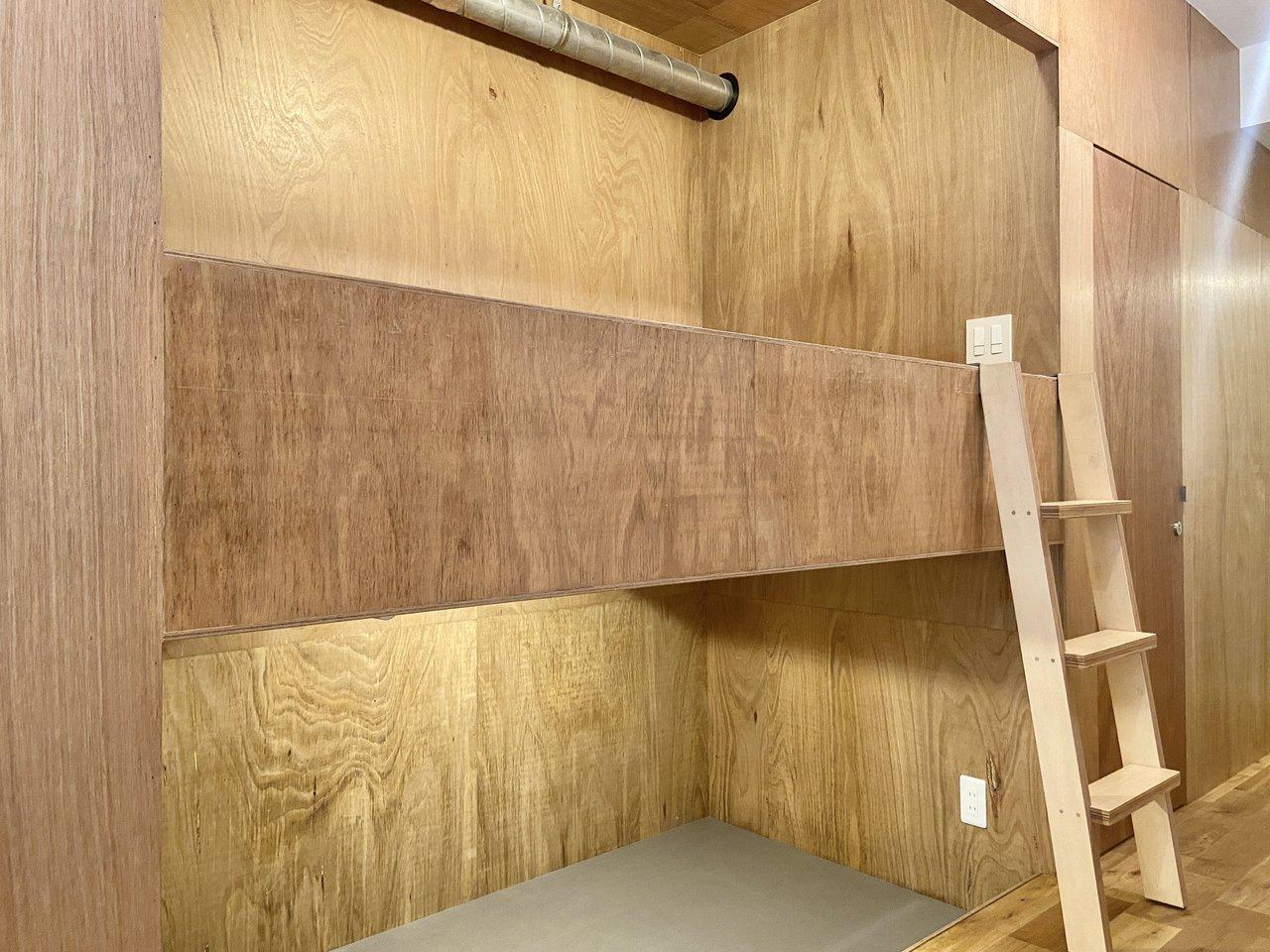 剥き出しの配管が秘密基地のようで心をくすぐられます。上はシングルサイズのマットレスを用意してベッド、下は収納として使えますよ。コンセントがあるのでスマホを充電しながら横になれますね。