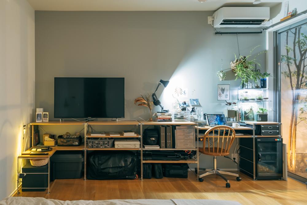 テレビ台、収納棚、ベッドサイドテーブル、ワークデスクとしての機能を持っているユニットシェルフ。壁一面を同じシステムで揃えることで整ってみえ、圧迫感を抑えることができたそう。(このお部屋はこちら)