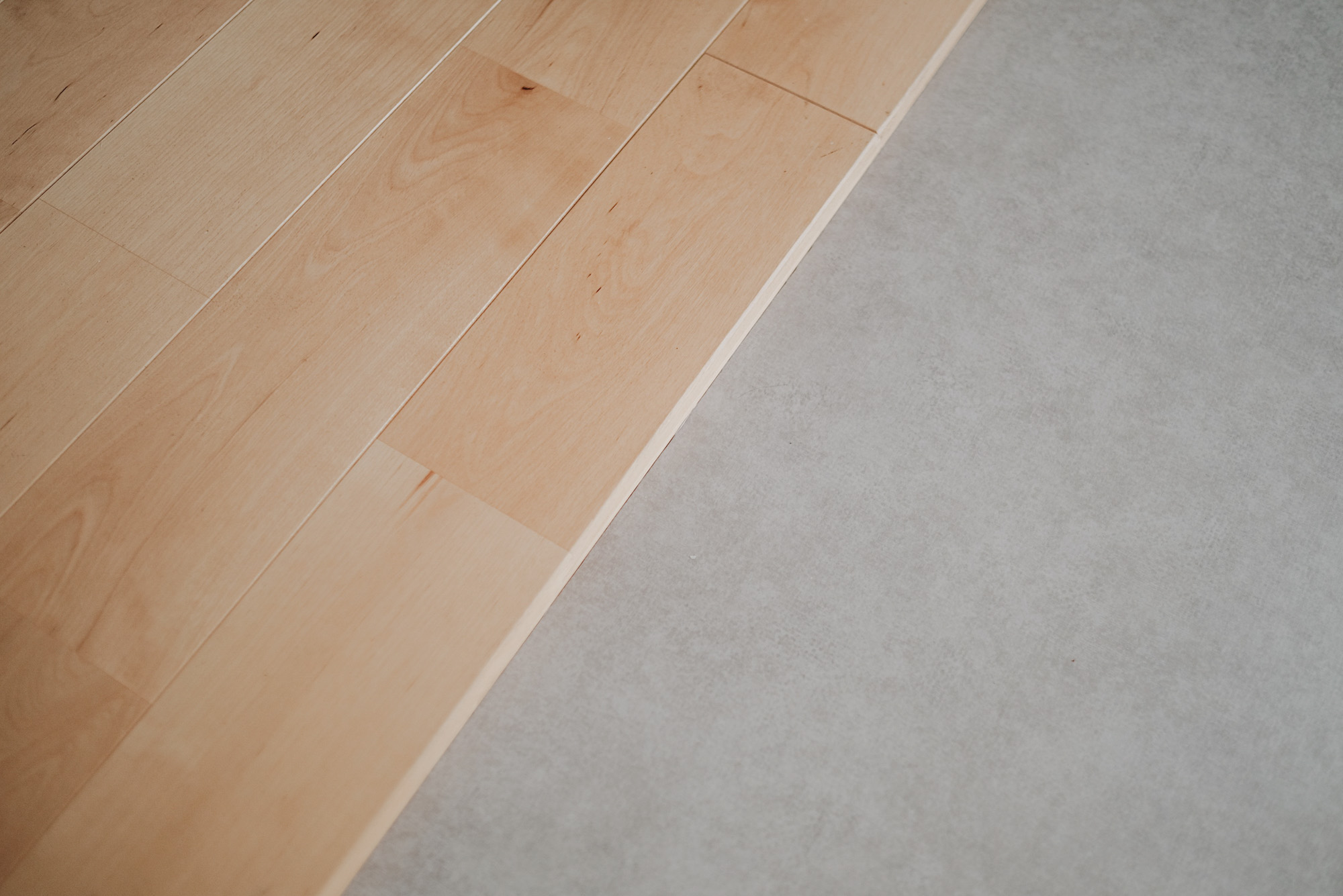 居室部分は、kannaさんも見てすぐに気に入られたという無垢フローリング。キッチン部分はモルタル風のフロアタイルと、床材を変えることでゆるく空間を区切っています。