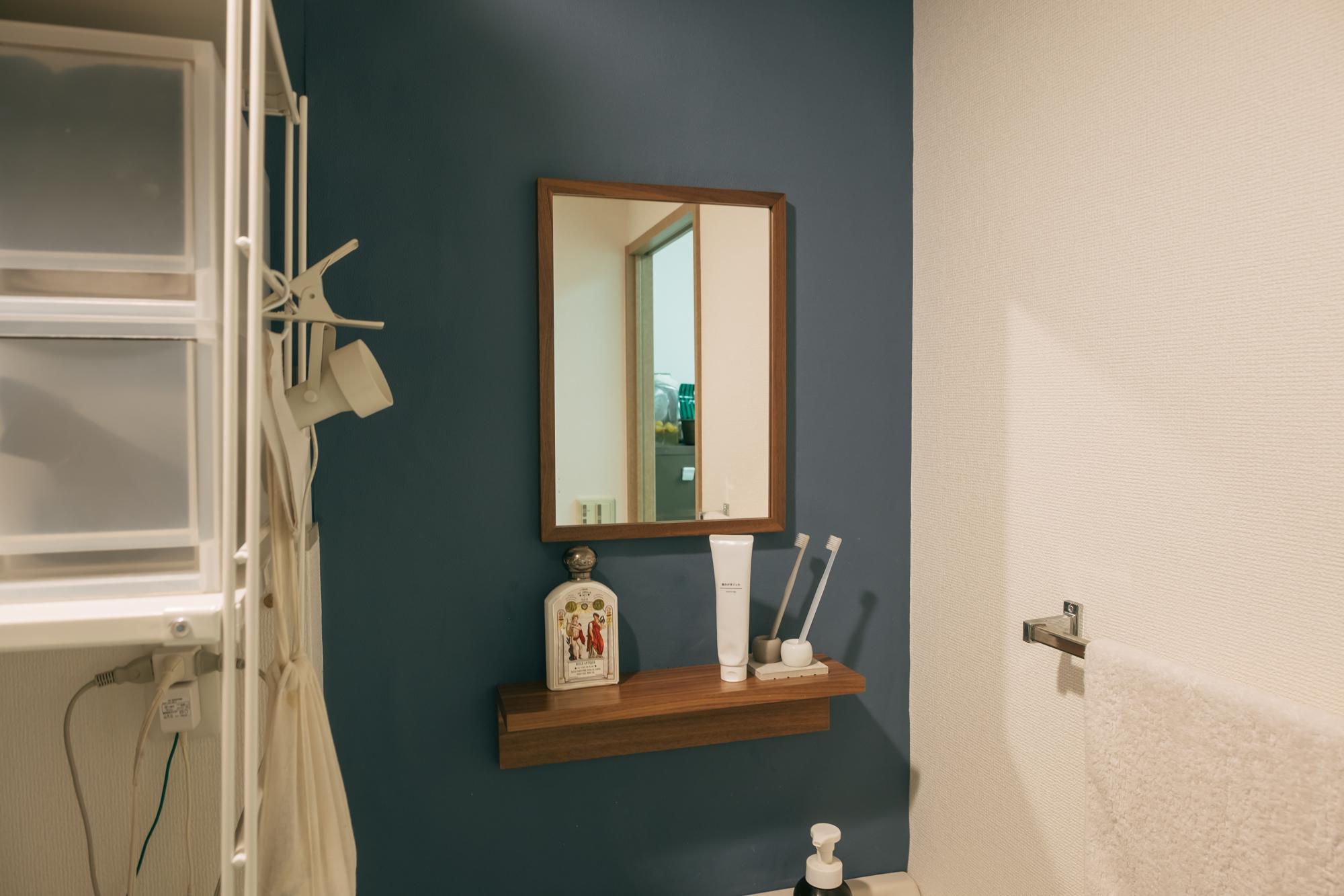 洗面台は、ちょっとごちゃごちゃして見えるミラーキャビネットを外してネイビーの壁紙と「壁に付けられる家具」を取り付けカスタマイズ。(※2)