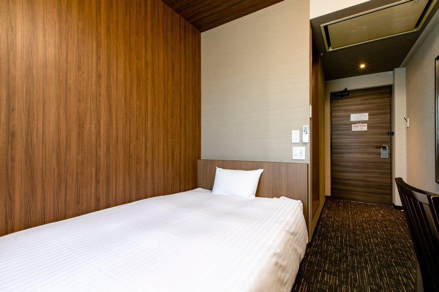 お部屋はシックなブラウンを基調としたシンプルなつくり。ベッドの向かいには、ワークデスクも完備されています。