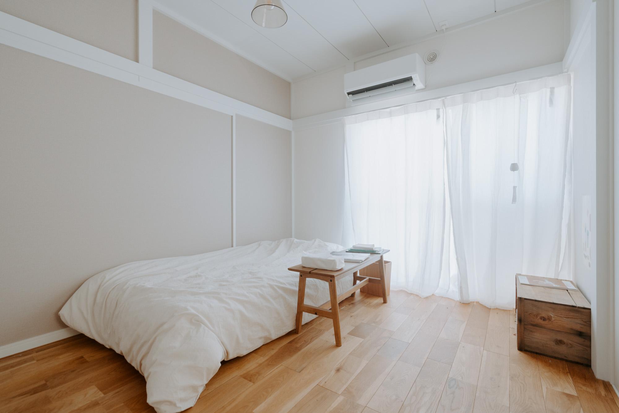 ベッドルームはシンプルに。ベッド横に置かれたベンチは、かなでもののオーク材のもの。床と同じ色味のものを選ばれています。
